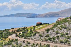 Coastal landscape of Croatie. Rocky coastal landscape of Croatia at the edge of a blue sea with some new houses Stock Images