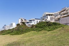 Coastal Landscape Beach and Sea at Umhlanga South Africa. Coastal landscape of green dune vegetation and lawn against commercial and residential buildings and Stock Photos