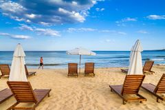 Coastal landscape - man saunter along the sea against the background beach umbrellas and loungers. The Kavatsi bay near city of Sozopol in Bulgaria royalty free stock image