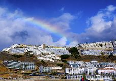 A coastal landscape from Puerto Rico in Gran Canaria. With a rainbow under a blue sky royalty free stock photo
