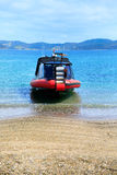 Coastal landscape with red motor boat on sandy beach. Stock Photos