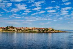 Coastal landscape - the rocky seashore with houses under the sky with clouds Royalty Free Stock Image