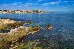 Coastal landscape - the rocky seashore with houses under the sky with clouds Royalty Free Stock Photography