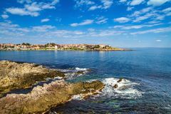 Coastal landscape - the rocky seashore with houses under the sky with clouds Stock Photos