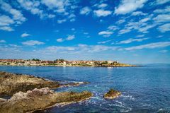 Coastal landscape - the rocky seashore with houses under the sky with clouds Royalty Free Stock Photos