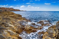 Coastal landscape - the rocky seashore with the village of Sozopolis Stock Image