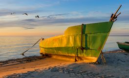 Fishing boat anchored at sandy beach during subrise Royalty Free Stock Photos