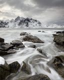 Coastal landscape in winter with water movement between big stones royalty free stock photography
