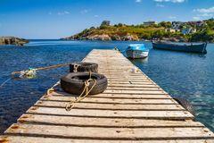 Coastal landscape - the wooden pier and boats in rocky bay Royalty Free Stock Photos