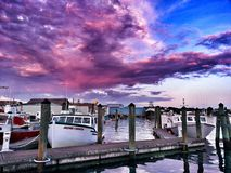 Coastal life. Amazing pink and purple sunset overlooking the pier Stock Photos