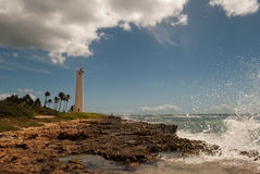 Coastal lighthouse. Wave hitting rocky coast, Barber's Point Lighthouse in the distance, Oahu, Hawaii Royalty Free Stock Photos