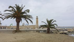 Coast lighthouse with two palm trees on the beach royalty free stock images
