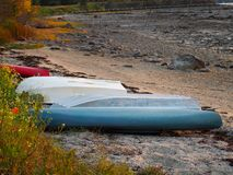 Coastal Maine Scene with Colorful Boats. A coastal Maine group of small colorful boats on a rocky and sandy beach royalty free stock photo
