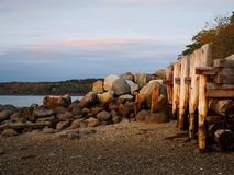 Coastal Maine Scene with Wooden Pilings. A coastal Maine sunset with wooden pilings on a rocky and sandy beach stock images