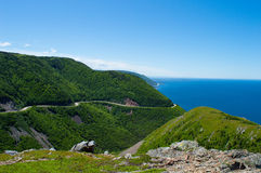 Coastal mountain. This in a beautiful bright green mountain with a winding road, which is set against a vibrant blue sky and ocean Stock Image