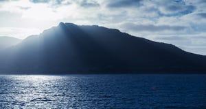 Coastal mountain landscape with sun beams Royalty Free Stock Image