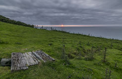 Coastal path wooden bridge, with a cloudy sky and bright sunset Stock Photo