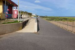 Coastal promenade, Chapel St. Leonards, Lincolnshire. Chapel St. Leonards, Lincolnshire, UK. October 08, 2018. Holidaymakers stroll the coast path promenade to stock image