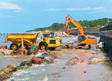 Coastal protection measures, construction equipment on the shore, the construction of breakwaters. Construction equipment on the shore, the construction of royalty free stock photography