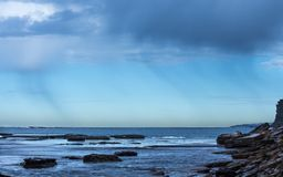 Coastal Rain falling over the ocean against blue sky with seaside rock ledge. In foreground Stock Photos