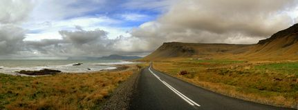 Coastal road in Iceland. Panoramic view of a coastal road in Iceland, spectacular sky royalty free stock images