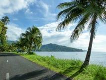 Coastal Road in Tropical Samoa. A blacktopped road hugs the coast around Samoa Royalty Free Stock Photos