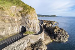 Coastal road with tunnel, Northern Ireland, UK. Causeway Coastal Route with Black Arc tunnel. Scenic road along eastern coast of County Antrim, Northern Ireland stock photo