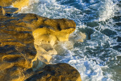 Coastal rocks lapped by the sea surf Stock Images