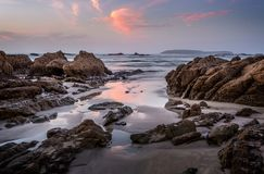 Coastal rocks and reflections in dawn hours stock photos