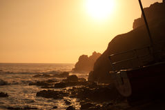 Coastal rocks and sea at sunset with boat on slipway Royalty Free Stock Photography