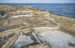 Coastal Salt Pans. Marsaskala, Malta. MARSASKALA, MALTA - AUGUST 1, 2015:  People relax on the shore near the historic salt pans in Marsaskala, Malta Royalty Free Stock Photography