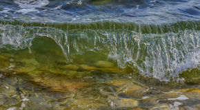 Coastal sea/ocean wave crashing on the beach. Coastal sea/ocean transparent wave crashing on the beach. Close up stock photo