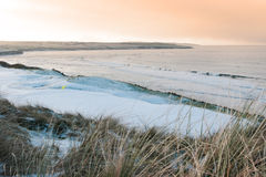 Coastal snow covered links golf course at sunset