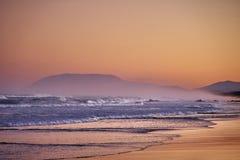 Coastal soft hazy sunset background. Coastal sea mist creating soft hazy warm glow over rolling waves on a sandy beach royalty free stock photography