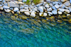 Coastal stones trough clear blue water Royalty Free Stock Image