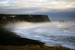 Coastal strip at Vik, Iceland. Coastal Strip with Black beach and cliff / rocks at Cap Dyrholaey with Reynisdrangar rock Formation in mist / fog in mystic royalty free stock image