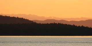 Coastal sunset. Several Sets of mountains fade off into the distance at sunset near Vancouver Island royalty free stock image