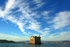 Liguria: coastal tower at sea under a cloudy sky view from the boat. Coastal tower at sea under a cloudy sky view from the boat, landcape with ligurian coast Royalty Free Stock Image