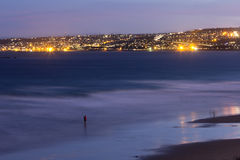Coastal town of Mossel Bay at night garden route. The coastal town of Mossel Bay as seen from across the bay.  There is a lone fisherman standing in the water Stock Photos