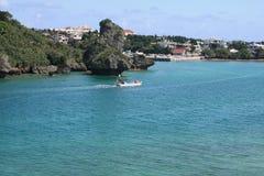 Coastal Village. A small boat on beautiful turquoise water passing a coastal village on Okinawa Stock Photo