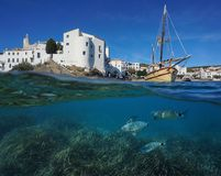 Coastal village boat with fish underwater Spain. Coastal village of Cadaques with a traditional boat and fish with seagrass underwater, split view above and Stock Photo