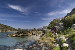 Coastal walk, Corsica. A men with backpack walking along the beach on coastal path in Corsica Royalty Free Stock Photography