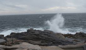 Coastal water crashing along the shoreline of Nova Scotia. That creates a spray that is quite high Stock Photos