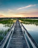 Vertical view of a beautiful sunset over coastal waters with a very long wooden boardwalk pier in the center during a colorful sum. Coastal waters with a very stock image