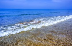 Coastal waves of clear blue sea water. Beach, yellow and white sand in sunny weather, blue sky, summer. Persian Gulf. Royalty Free Stock Photos