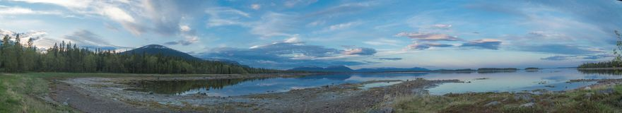 Panorama of low tide in the Kandalaksha Bay. Coastal wooded islands and calm sea in the Kandalaksha Bay royalty free stock photo