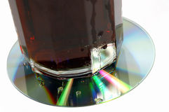 Coaster. A soft drink resting on a defective cd-rom Royalty Free Stock Photos