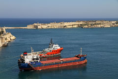 Coaster and tugboat in Valletta Stock Photo