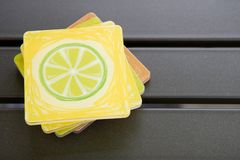 Coasters. Colorful coasters on patio table stock image