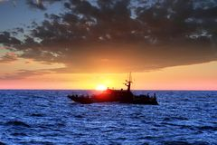 Coastguardsegling under solnedgången royaltyfri foto